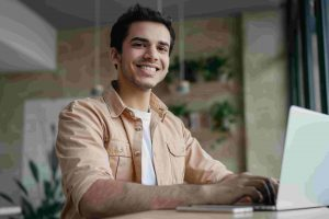 smiling-freelancer-copywriter-using-laptop-working-from-home-min