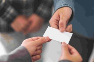 two-businessman-holding-exchanging-empty-business-card-min